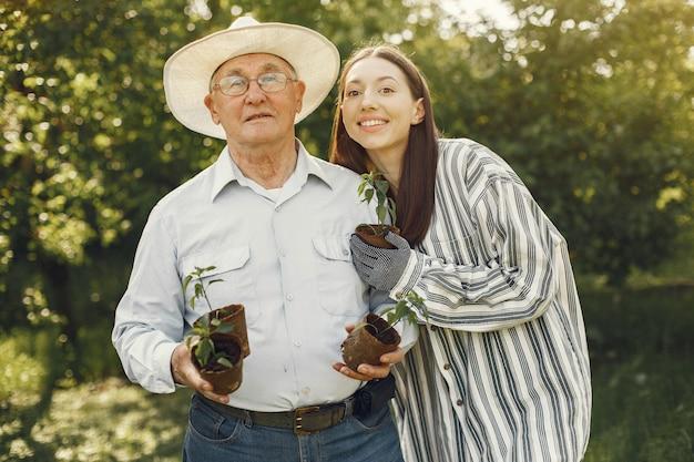 Portrait of senior man in a hat gardening with granddaugher