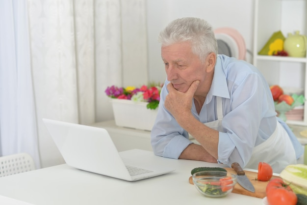 Portrait of  senior man  in the kitchen with laptop at home