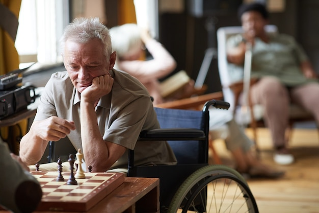 Portrait of senior man playing chess and enjoying activities in nursing home copy space