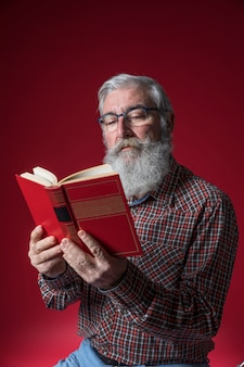 Portrait of a senior man reading the book holding in hand against red background