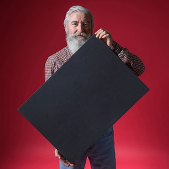 Portrait of a senior man showing blank black placard standing against red backdrop