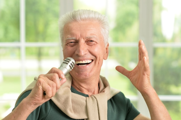 Portrait of a senior man singing into microphone