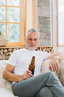 Portrait of senior man sitting on sofa looking at camera holding beer bottle