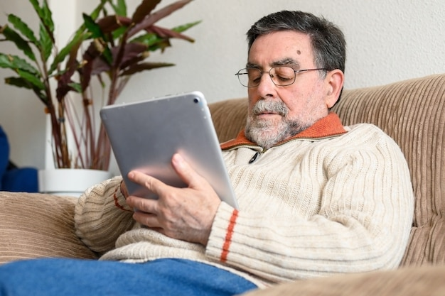 Portrait of senior man sitting on sofa and using digital tablet in living room.