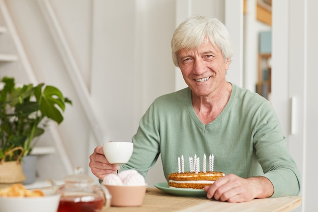 Portrait of senior man smiling at camera while sitting at the table with tea and birthday cake