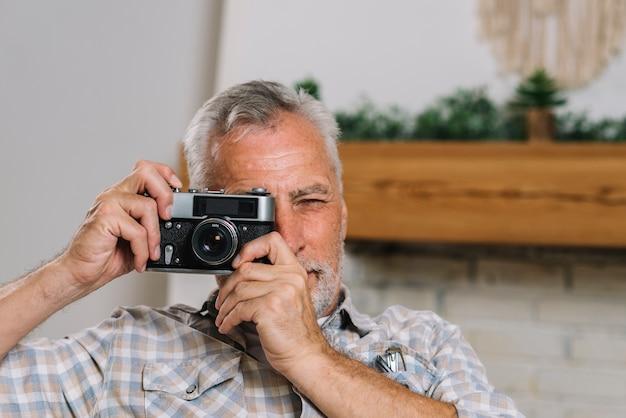 Portrait of senior man taking photo from camera