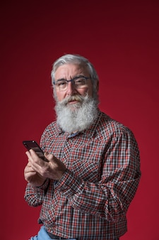 Portrait of a senior man wearing eyeglasses holding smart phone in hand against red backdrop