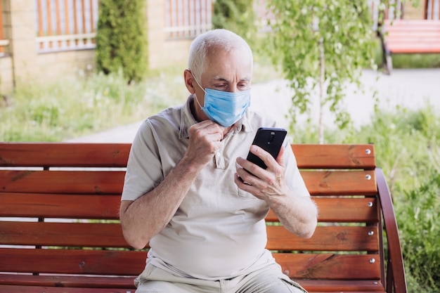 Portrait of senior man wearing medical mask with mobile phone. coronavirus concept. respiratory protection