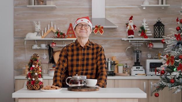 Portrait of senior man wearing santa hat smiling while looking into camera during christmas morning