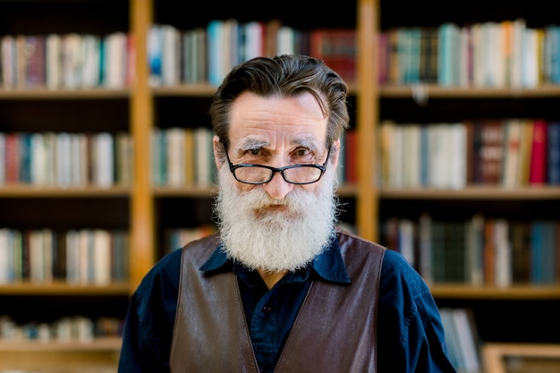 Portrait of senior man with beard and eyeglasses, looking at camera, standing on book shop market background. library, reading concept