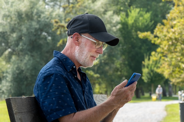 Portrait of senior man with beard and glasses using smartphone