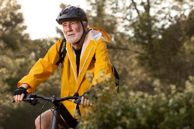 Portrait senior man with bike on mountain