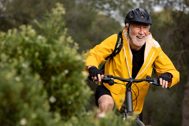 Portrait senior man with bike on mountain