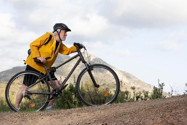 Портрет старшего мужчины с велосипедом на горе Бесплатные Фотографии