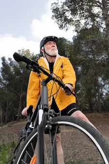 Портрет старшего мужчины с велосипедом на горе