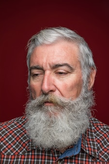Portrait of senior man with grey bearded against dark colored background