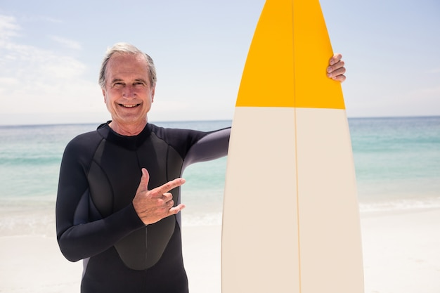 Portrait of senior man with surfboard gesturing hand sign at beach