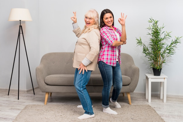 Portrait of senior mother and her young adult standing back to back showing ok sign
