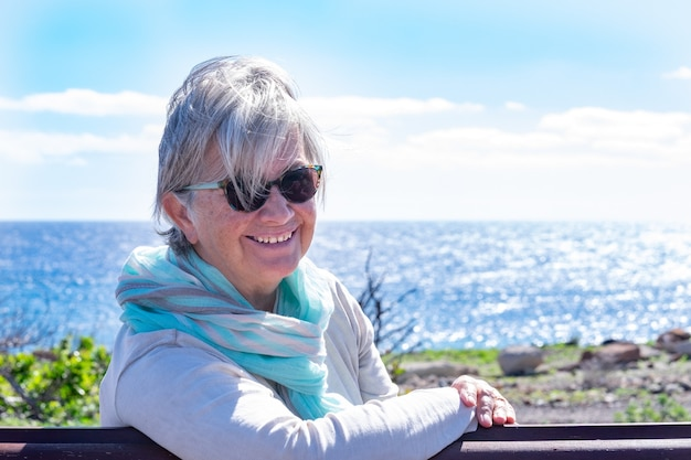 Portrait of a senior smiling woman relaxing in front to the sea, sitting on a bench looking at the camera. senior woman enjoying retirement and outdoors