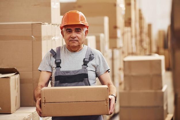 Portrait of senior storage worker in warehouse in uniform and hard hat.