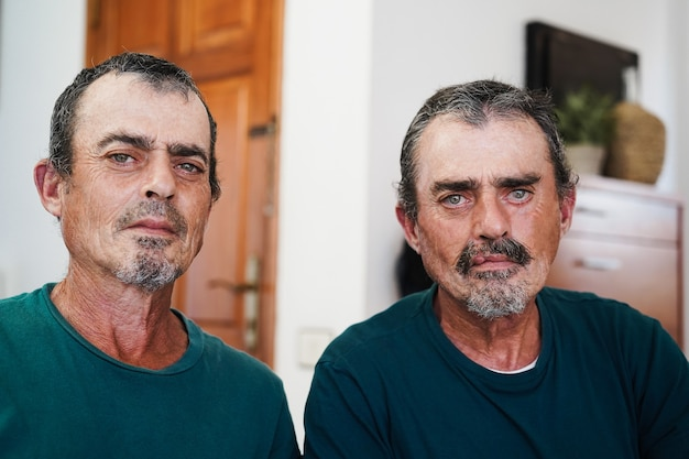 Portrait of senior twin men smiling  indoors at home - focus on faces