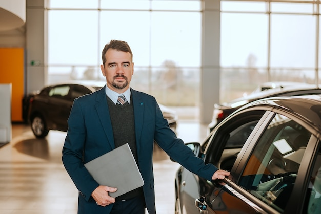 Portrait of senior vehicle salesman working at a car dealer.
