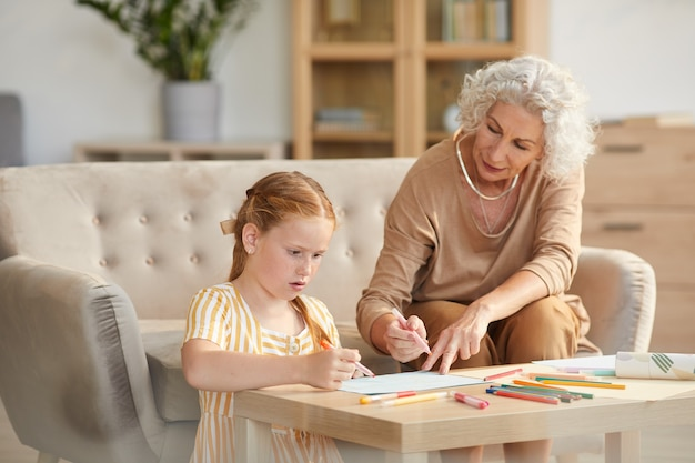 Portrait of senior woman babysitting cute red haired girl and drawing together while sitting in cozy living room