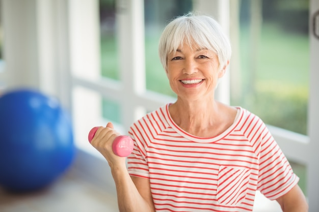 Portrait of senior woman exercising with dumbbell at home