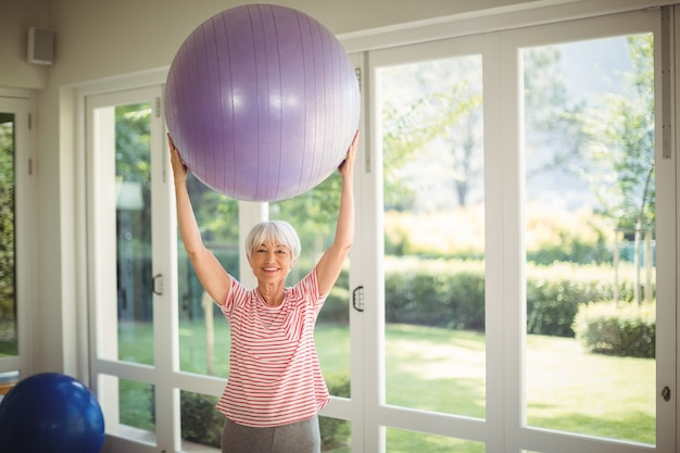 Portrait of senior woman exercising with fitness ball