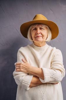 セーターと帽子の肖像画の年配の女性。白いニットのセーターと帽子のスタイリッシュな高齢女性