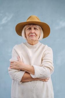 Женщина портрета старшая в свитере и шляпе. стильная женщина в возрасте в белом вязаном свитере