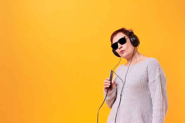 Portrait of senior woman listening music with copy space