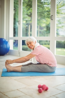 Portrait of senior woman performing stretching exercise at home