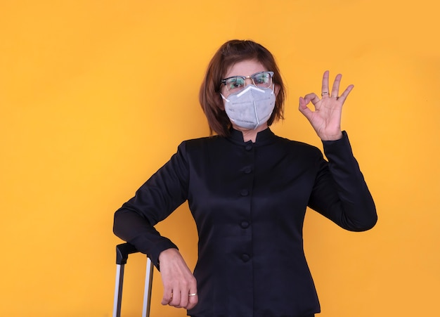 Portrait of senior woman showing ok sign and wearing mask