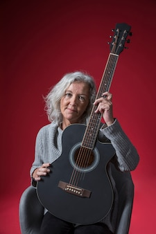 Portrait of a senior woman sitting on chair holding guitar against red background