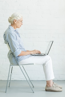 Portrait of senior woman sitting on chair using laptop