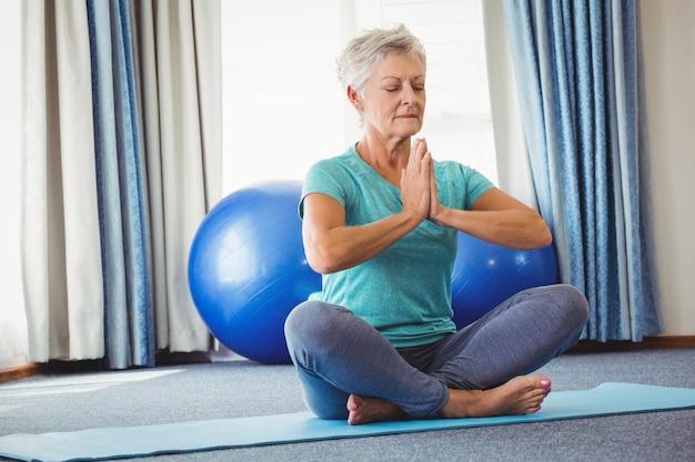 Portrait of senior woman sitting in lotus position