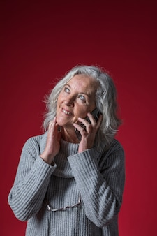 Portrait of a senior woman talking on mobile phone looking up against red background