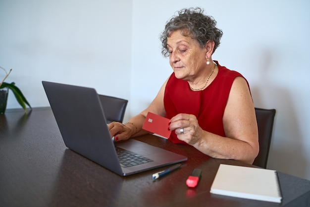 Portrait of senior woman using credit card to buy online