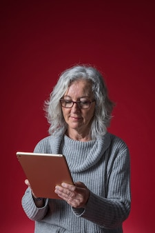 Portrait of a senior woman using digital tablet against red backdrop