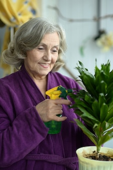 Portrait of a senior woman watering plant at home