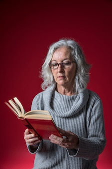 Portrait of a senior woman wearing eyeglasses reading the book standing against red background