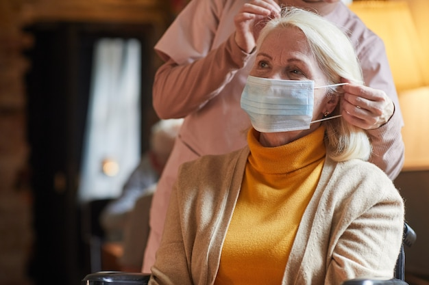 Portrait of senior woman wearing mask in retirement home with nurse assisting her copy space