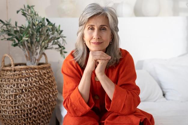 Ritratto di donna anziana che indossa una camicia rossa