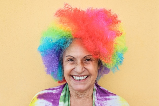 Portrait of senior woman wearing wig with yellow wall - focus on face
