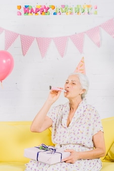Portrait of a senior woman with birthday gift sitting on sofa blowing party horn