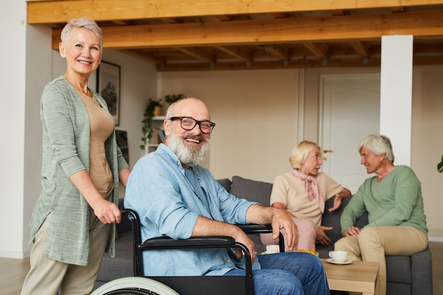 Portrait of senior woman with disabled man in wheelchair smiling at camera with other people