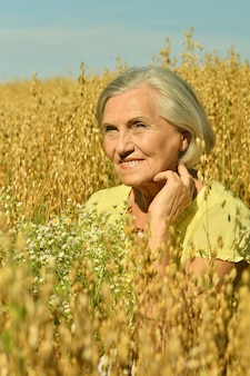 Portrait of a senior woman with flowers in field
