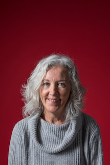 Portrait of a senior woman with short grey hair against red background