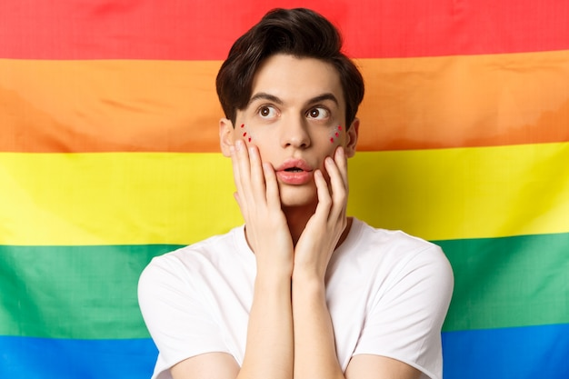 Portrait of sensual and beautiful gay man with glitter makeup on face, looking at upper left corner excited, standing against lgbtq rainbow flag.